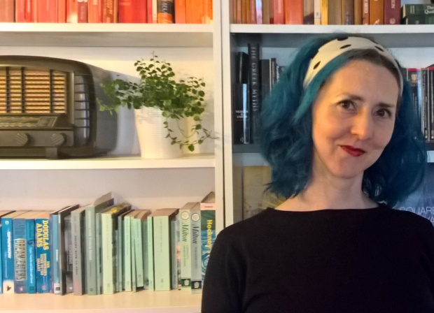 Georgi with blue hair and a black and white hair scarf, wearing a black sweater. She is smiling and standing in front of shelves with brightly coloured books, a plant and a vintage radio.